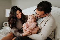 Couple with baby daughter on bed in bedroom - ISF21118