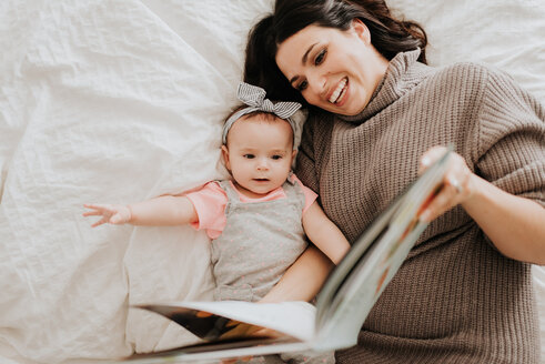 Mother reading with baby daughter on bed - ISF21133