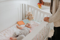 Father putting baby daughter to bed in crib - ISF21139
