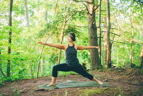 Woman doing warrior pose in forest - ISF21151