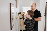 Father teaching son drill wall for picture frames - ISF21205