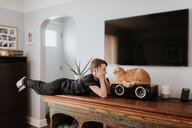 Boy staring at cat on cabinet - ISF21208