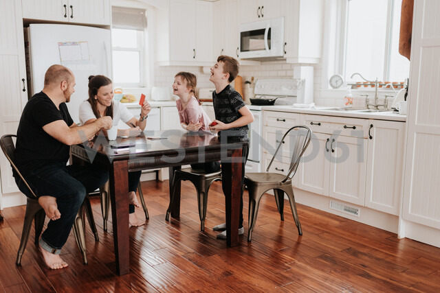 Family of four playing cards in kitchen - ISF21211
