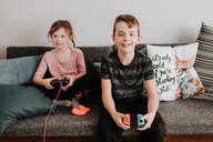 Children playing video game on couch - ISF21214