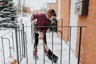 Girl shovelling snow on porch - ISF21226