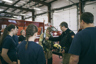 Firefighters meeting, checking equipment in fire station - HEROF35554