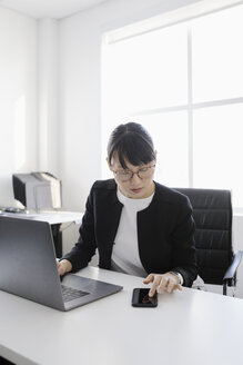 Businesswoman at laptop using smart phone in office - HEROF35581