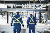 Male workers carrying bucket below gas plant pipelines - HEROF35611