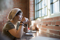 Pensive young woman drinking coffee in coffee shop - HEROF35614