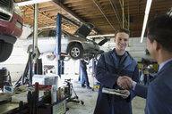 Mechanic and customer shaking hands auto repair shop - HEROF35635