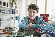 Portrait confident boy assembling circuit board in bedroom - HEROF35644