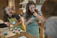 Playful girls with frosting on nose baking cupcakes - HEROF35650