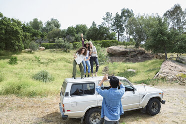 Man photographing young women on top of car - HEROF35659