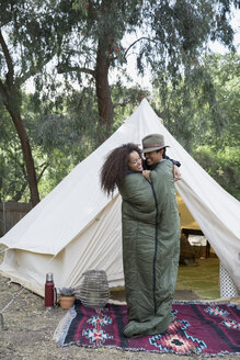 Playful couple sharing sleeping bag outside camping yurt - HEROF35662