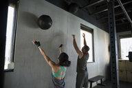 Man and woman throwing medicine ball at wall - HEROF35683