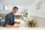 Focused businessman using laptop at office desk - HEROF35698