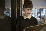 Focused young businesswoman using digital tablet - HEROF35704