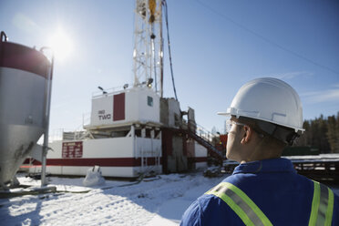 Male worker looking up at drilling rig snow - HEROF35719