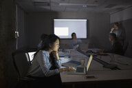 Focused businesswoman using laptop dark conference room meeting - HEROF35782
