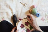 Close-up of woman embroidering strawberry pattern - IGGF01023
