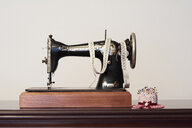 Old vintage sewing machine with measuring tape and pin chusion in shape of a hat - IGGF01026