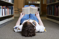 Female student reading book in a public library, lying on the ground - IGGF01047