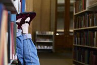 Female student in a public library, feet up - IGGF01059