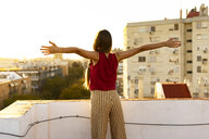 Rear view of teenage girl standing on roof terrace in the city at sunset - ERRF00939
