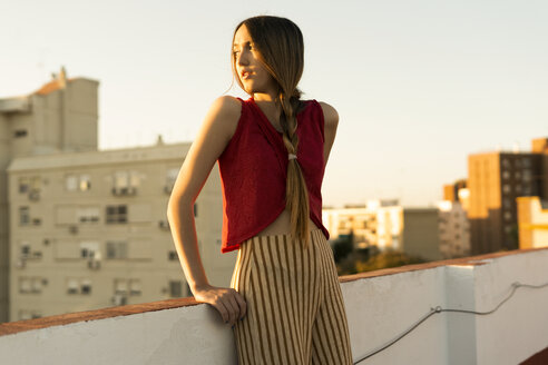 Teenage girl standing on roof terrace in the city at sunset - ERRF00945