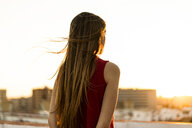 Rear view of teenage girl on roof terrace in the city at sunset - ERRF00960