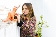 Girl playing with dinosaur toy at home - ERRF00972