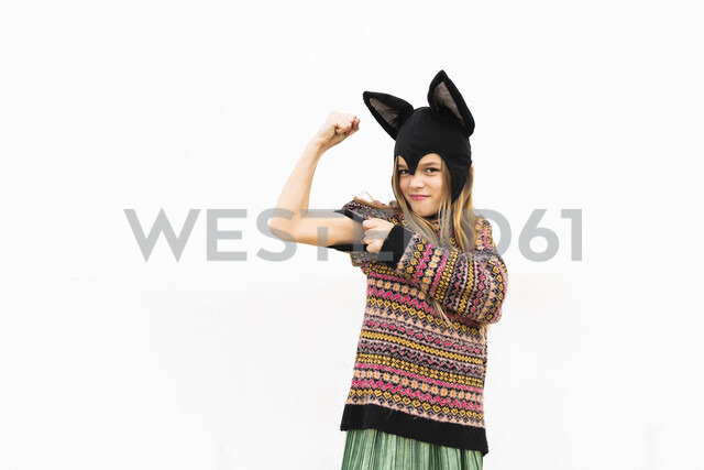 Portrait of girl flexing muscles in bat costume in front of white wall - ERRF00987 - Eloisa Ramos/Westend61