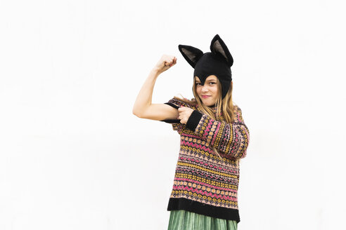 Portrait of girl flexing muscles in bat costume in front of white wall - ERRF00987