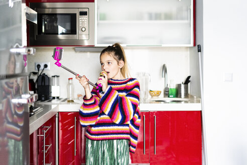 Girl playing with microphone and smartphone in kitchen at home - ERRF00996