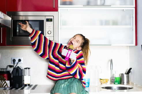 Girl playing with microphone and smartphone in kitchen at home - ERRF00999