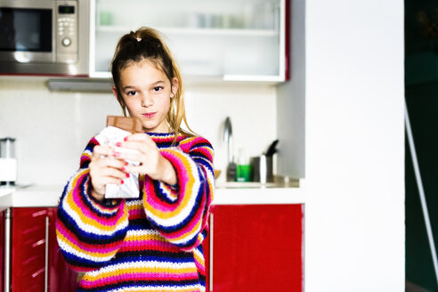 Portrait of girl in striped pullover in kitchen at home eating chocolate - ERRF01002