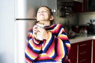 Girl in striped pullover in kitchen at home eating chocolate - ERRF01005