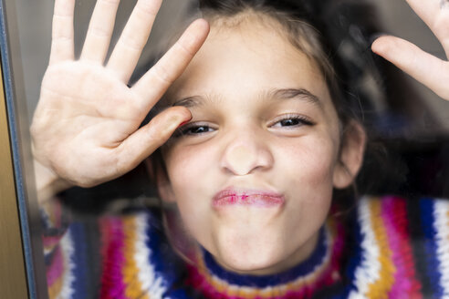 Portrait of happy playful girl in striped pullover behind windowpane - ERRF01008
