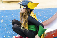 Girl in super heroine costume on playground slide - ERRF01023