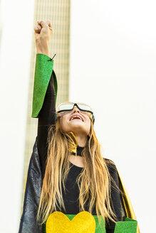 Girl posing in super heroine costume clenching fist - ERRF01032