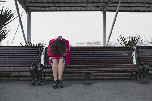 Depressed woman with curly hair sitting on a bench - EYAF00125