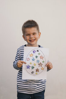 Boy holding his art work and smiling - MOMF00680