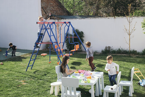 Kids playing in a garden, paining Easter eggs, climbing on swing - MOMF00695
