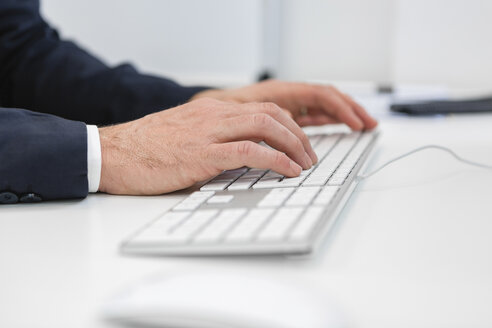 Close-up of businessman using computer keyboard at desk in office - MGIF00372
