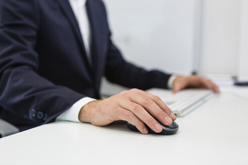 Close-up of businessman using computer at desk in office - MGIF00378