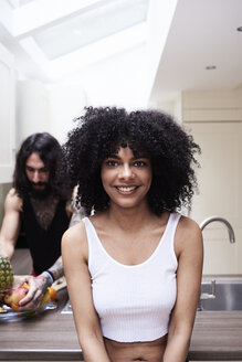 Portrait of smiling young woman with boyfriend in kitchen - IGGF01088