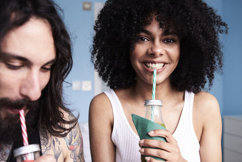 Portrait of smiling young woman with boyfriend drinking smoothie - IGGF01097