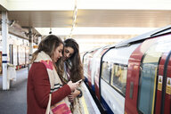 UK, London, two women using cell phone at underground station platform - IGGF01103