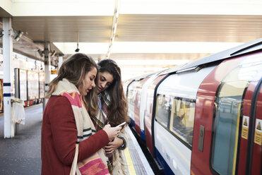 UK, London, two women using cell phone at underground station platform - IGGF01103