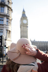 UK, London, rear view of woman wearing a floppy hat looking at Big Ben - IGGF01115